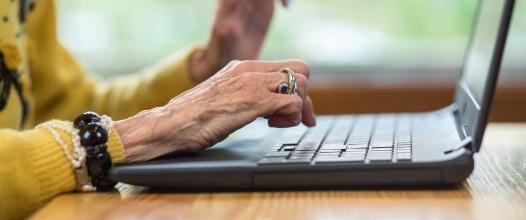 Staré vrásčité ruce píšící na klávesnici notebooku